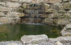 Stone wall and pond detail Stock Images
