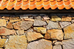 Stone wall with red clay roof. Stone wall house with red red clay roof tile architecture detail Stock Image