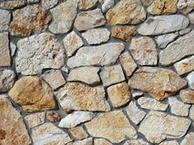 Stone wall reinforced with cement, in shades of brown and beige, in natural light. Wall of raw natural stone shades of brown.reinforced with cement stock image