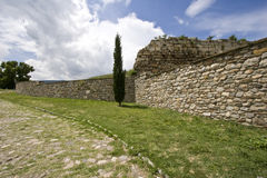 Stone Wall and Road. At the top of a grassy hill, a stone path or road skirts the edge of a hand laid stone wall in Skopje, Macedonia, near the Skopje or Kale Royalty Free Stock Photos