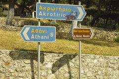 Stone wall and road signs in Greece Royalty Free Stock Photo