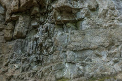 The stone wall of rock with cracks. The stone wall of a rock with cracks Stock Image
