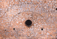Stone wall with round window and metal bars, of an ancient fortress. Stock Photos