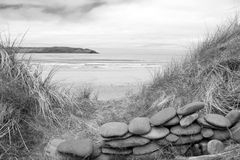 Stone wall shelter on a beautiful beach in black and white stock images