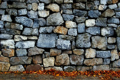 Stone wall and sidewalk with autumn leaves Royalty Free Stock Photos