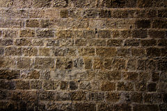 Stone wall in spotlight. Background of a battered medieval wall in spotlight Stock Photo