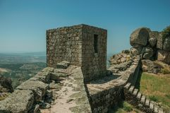 Stone wall and square tower on hilltop at the Castle of Monsanto. Stone wall with staircase and square tower on hilltop and countryside landscape, in a sunny day royalty free stock photos