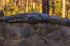 Stone wall and sunlit trees Royalty Free Stock Photos