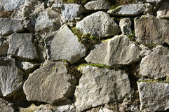 Stone wall texture. Ancient rough stone walling with moss texture as background Royalty Free Stock Images