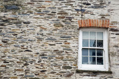 Stone wall texture background with sash window. A light coloured Cornish stone wall with lichen and moss and a sash window Stock Photo