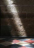 A stone wall and a tiles floor, with a blade of light Royalty Free Stock Photos