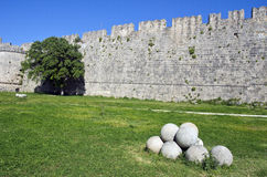 Stone wall,  tree and pile round stone objects in Greece Stock Photo