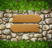 Stone wall with two wooden arrows Royalty Free Stock Photos