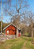 Stone wall and a typical red house in sweden. Royalty Free Stock Images
