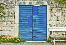 Stone wall, vintage blue gate and wooden bench royalty free stock photography