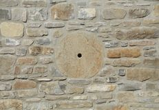 Stone wall in warm colors with grinding wheel. In the middle Stock Photo
