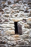 Stone wall with window. Small window in stone wall in old building Royalty Free Stock Images