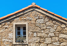 Stone wall with window under red tile roof Stock Photo