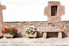 Stone wall with windowand stone benchon a street adorned with flower pots. Small window adorned with stones and bars on a whitewashed wall of white with bjos of Royalty Free Stock Images