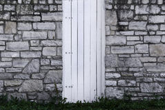 Stone Wall and Wood Gate. An old stone wall with a white, wooden gate Stock Photo