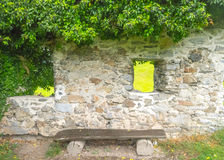 Stone wall with wooden bench Stock Images
