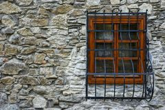 Stone wall, wooden window frame and steel grillage Royalty Free Stock Photo