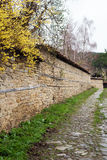 Stone Wall and yellow flowers. Street with cobble stones of folk museum Zheravna village in Bulgaria. Mountain village Royalty Free Stock Photo