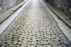 Stone walled cobbled street. Old cobbled street with stone walls Stock Images