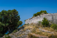 Stone walls of ancient fortress up the hill Stock Photo