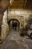Stone walls and communication tunnels between underground stone cellars where La Rioja wine ages in old oak barrels. With people v. Isiting them stock image