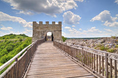 Stone walls and gate with wooden bridge on medieval fortress Stock Image