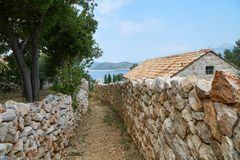 Stone walls and path. Narrow stone walls and path leading to sea. Stone house with red tile roof. Trees and garden stock photography