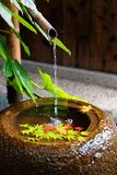 A stone washbasin  chozubachi  by a Japanese tea room, with a bamboo pipe supplying water & colorful maple leaves fallen on the Royalty Free Stock Images