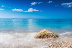Stone washed by the waves and the boat sails Royalty Free Stock Image