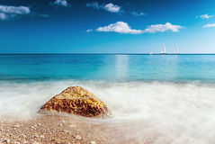 Stone washed by the waves and the boat sails on the horizon Stock Photos