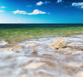 Stone washed by the waves and the boat sails on the horizon Stock Image