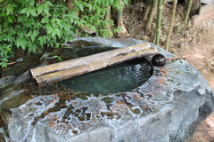 Stone water basin with water from bamboo pipe. Royalty Free Stock Images