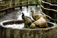 Stone water feature in the shape of two elephants,. Spurting water into a receptacle Stock Images