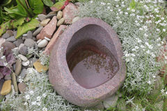Stone water pot with arrangement Royalty Free Stock Images