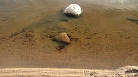 Stone in water on shore of lake stock footage