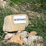 Stone with a white no entrance sign lettering in a green grass field royalty free stock photo