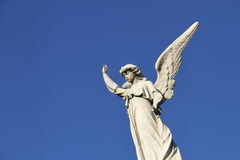 Statue of the Guardian angel in the blue sky. Creed. Stone white statue of the Guardian angel against the blue sky Stock Photo