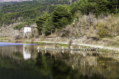 Stone wind mill and wooden pier reflection on Cubuk lake near Goynuk Royalty Free Stock Photo