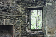 Stone window. Rundown old stone house with window view of trees royalty free stock photo