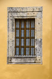 Stone window frame and yellow wall Royalty Free Stock Photography