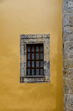 Stone window frame and yellow wall Stock Photography