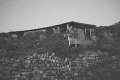 Stone and wood shed built into rocky hillside Royalty Free Stock Photos