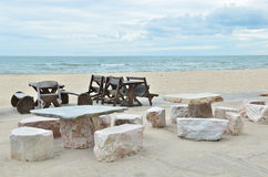 Stone and Wooden chair on beautiful beach Stock Image