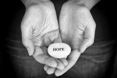Stone with the word Hope in the woman's palms Royalty Free Stock Images