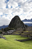 Stone Works Machu Picchu Peru And Peak Huayna Picchu. Inca Stone Work At Machu Picchu Peru With Peak Huayna Picchu Green Lawns Mountains And Clouds Vertical royalty free stock photography